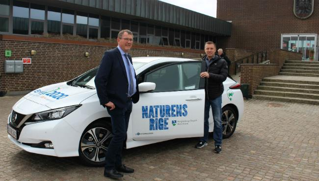 Borgmester Hans Østergaard og formand for Energirådet Jakob Agerbo på vej ud i kommunens nye elbil.